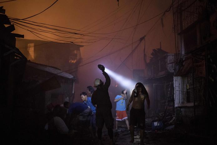 Een brandweer man in de Filipijnse hoofdstad Manila schijnt met zaklamp in een huis na een grote brand in een sloppenwijk. Honderden inwoners moesten worden geëvacueerd.  Foto: Noel Celis