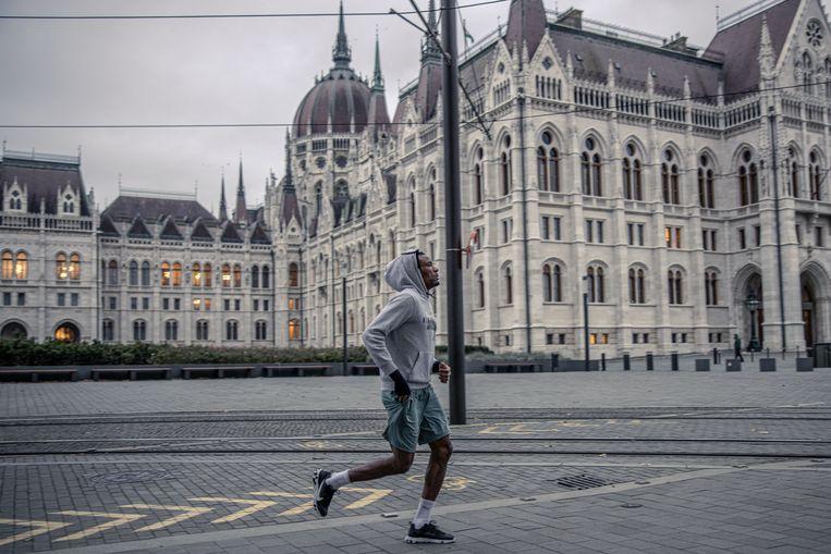 Een hardloper voor het parlement van Hongarije in Boedapest. Beeld Akos Stiller