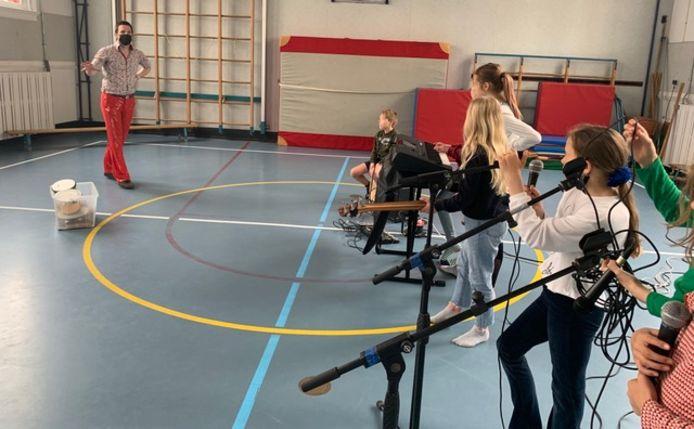 Medewerker van de Stadsschouwburg Adam Thomassen geeft muziekles aan kinderen van openbare basisschool De Koekoek.