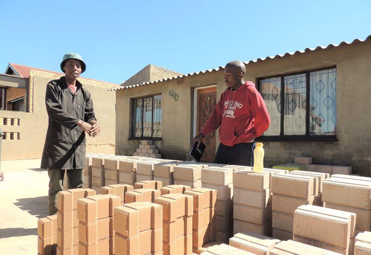 Zakenpartners Nhlanhla Ndlovu (links) en Terry Mathebula bakken hun bakstenen zelf. Beeld Niels Posthumus
