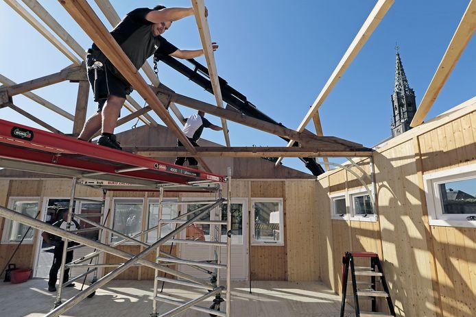 Vrijwilligers monteren het bouwpakket voor een tijdelijk paviljoen naast de Overlangelse kerk.