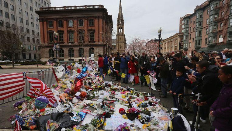 Mensen leggen bloemen en kaarten neer bij een herdenkingsplek in Boston. Beeld afp