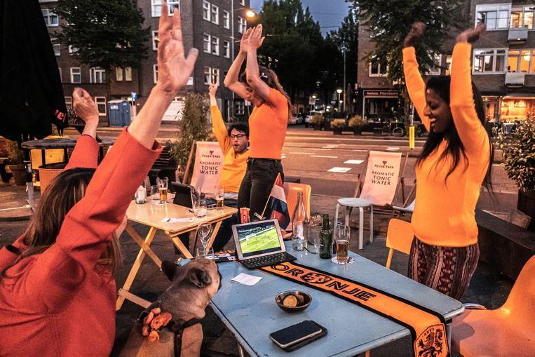 Voetbalfans kijken de EK-Wedstrijd, Nederland - Oekraïne op eigen meegenomen tablets op het buitenterras van Bar BAUT aan de Stadionweg in Amsterdam.  Beeld Joris van Gennip