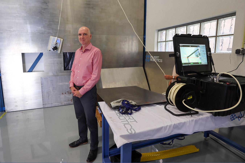 Directeur Neil Fletcher van Invert Robotics bij een demonstratiewand met inspectierobot. Op de monitor kan de robot worden gevolgd.
