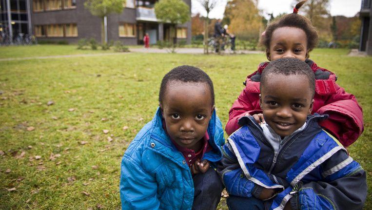 Kinderen van asielzoekers op het terrein achter het hoofdgebouw van Centraal Orgaan opvang asielzoekers (COA) in Amersfoort. Beeld ANP