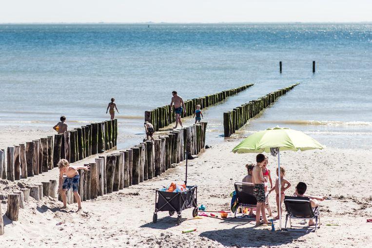 Spelende kinderen tussen de paalhoofden op het strand in Zoutelande. Beeld Tine Schoemaker