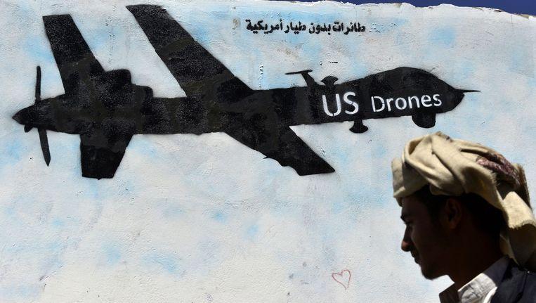 Een Jemenitische man loopt langs een muur in een straat van Sanaa waarop een Amerikaanse drone is getekend. Beeld anp