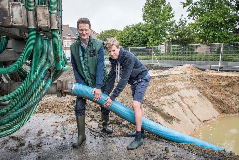 Landbouwer Johan Hanssens en zijn zoon pompen water van de AZ Delta-site op.