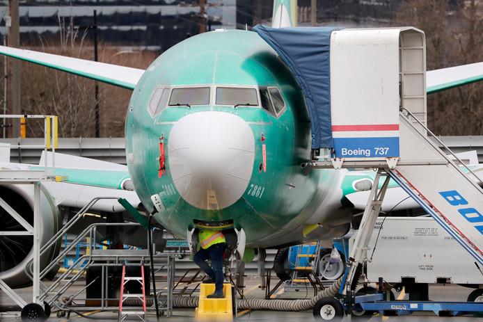 Een technicus aan het werk onder de neus van een Boeing 737 Max.