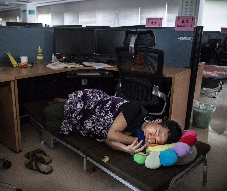 Een werknemer van Huawei rust uit tijdens de lunchpauze. Beeld Getty