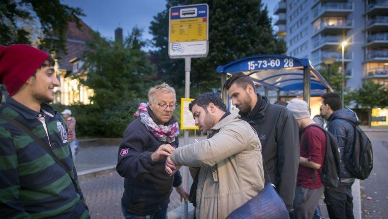 Vrijwilligster Alberta van den Hemel helpt bij de bushalte in Emmen. Beeld Herman Engbers