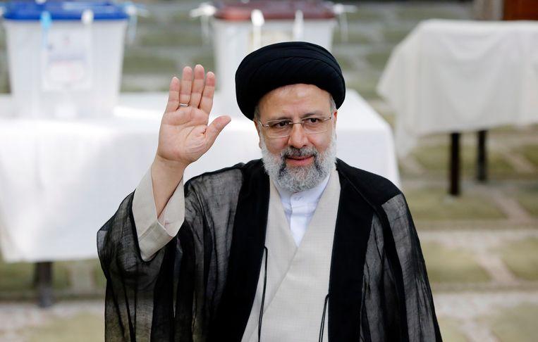 Ebrahim Raisi groet de media naar het uitbrengen van zijn stem in een moskee in Shahre Ray, ten zuiden van Teheran.  Beeld EPA
