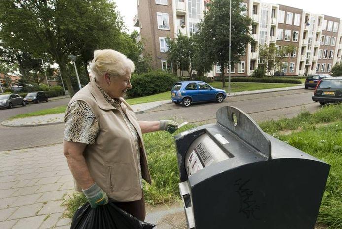 Een Arnhemse bij een ondergrondse container in de wijk Geitenkamp. De vrouw speelt geen rol in het verhaal.