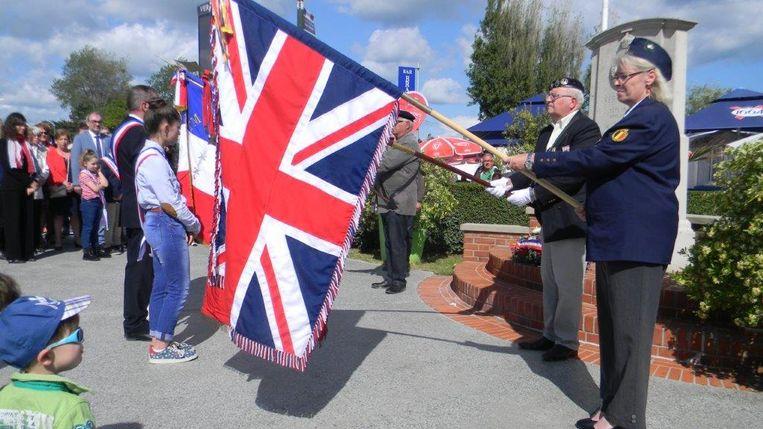 Dochter Nadia draagt het Engelse vaandel aan één van de drie monumenten in Ver-sur-Mer.