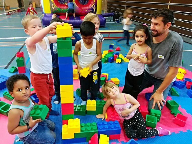 De kinderen bouwen een toren met blokken.