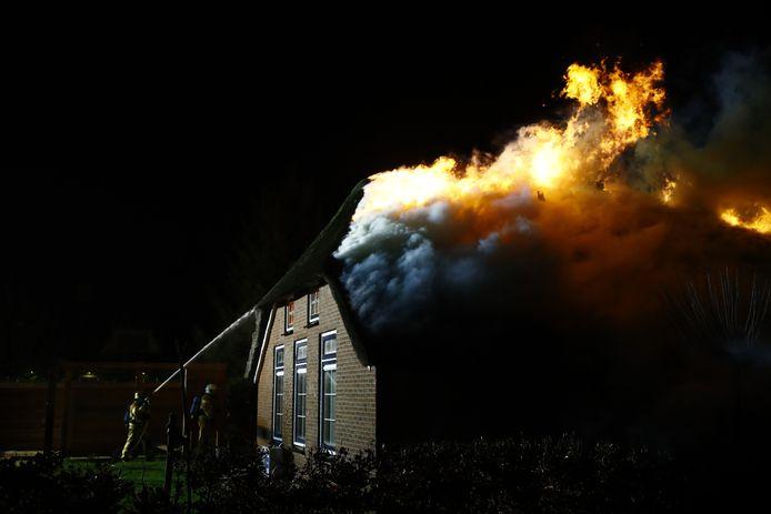 De vlammen slaan uit het dak van de woning in Oldebroek.