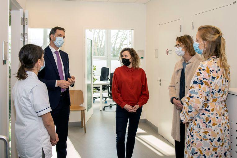 Premier Alexander De Croo en staatssecretaris voor Gelijke Kansen Sarah Schlitz (m.) bezoeken een Zorgcentrum na Seksueel Geweld in UZ Gent in maart. Beeld Photo News