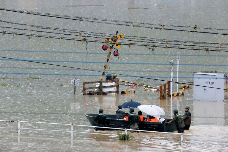 Reddingswerkers proberen bewoners die getroffen zijn door het noodweer te evacueren. Beeld AP