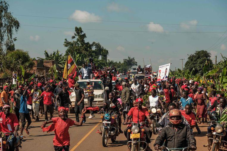 Presidentskandidaat Robert Kyagulanyi, beter bekend onder zijn artiestennaam Bobi Wine, omringd door aanhangers op campagne dit jaar.  Beeld AFP