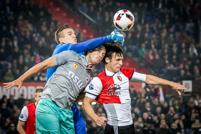 Excelsior keeper Filip Kurto stompt de bal weg voor Feyenoord speler Eric Botteghin met in het midden Excelsior speler Jurgen Mattheij.