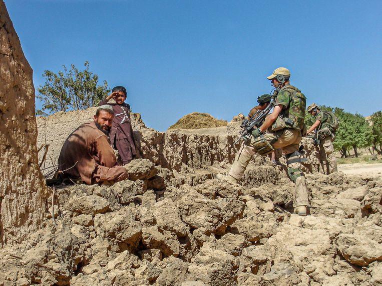 Twee maanden na de bombardementen bezoeken Nederlandse militairen het zwaar getroffen dorpje Qal-e-Ragh om de schade op te nemen en claims uit te betalen. Beeld Noël van Bemmel