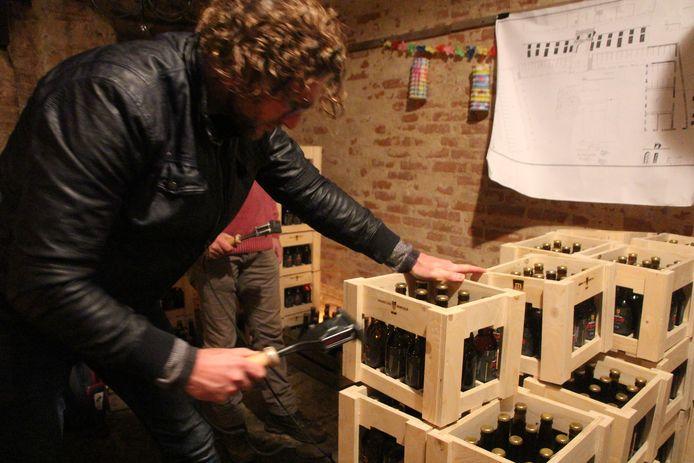 Menno van Bree voorziet een kratje van het brandmerk-logo 'Heeren van Borculo', in de kasteelkelder waar het eerste bier zaterdag wordt uitgegeven.