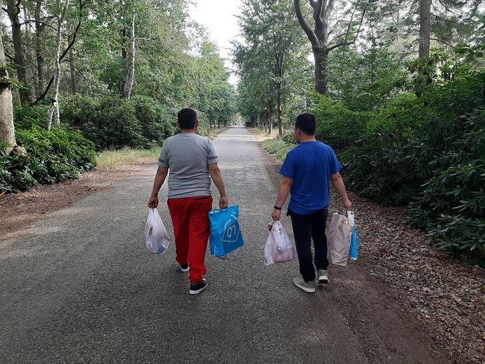Twee Afghanen  lopen met tassen vol etenswaar terug naar de noodopvang in Heumensoord.