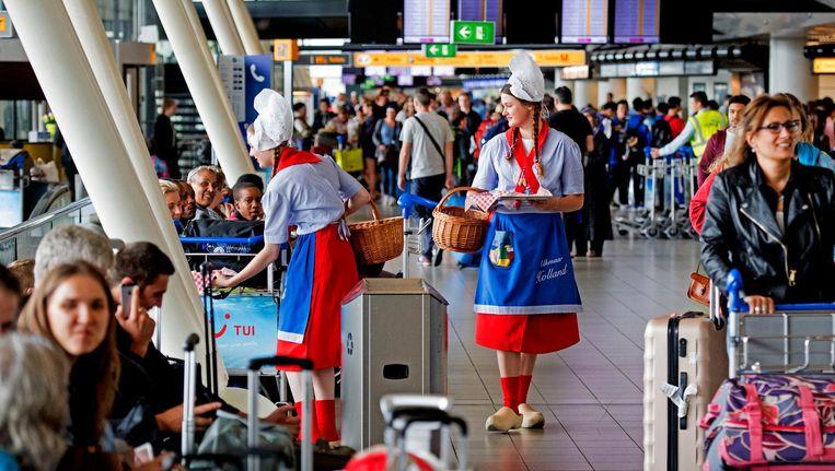 Alkmaarse kaasmeisjes delen blokjes kaas uit aan reizigers op de luchthaven. Beeld anp