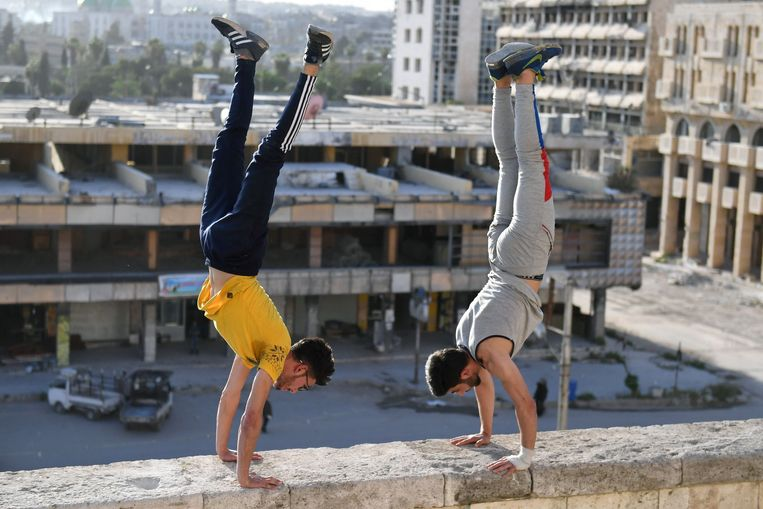 TOPSHOT - Syrian youths practise parkour in Aleppo, northern Syria, on April 7, 2018. In the absence of special facilities and equipment for the sport, such as padding to protect against falls, athletes often risk serious injury. And parkour in east Aleppo comes with an additional challenge: remnants of war.  / AFP PHOTO / George OURFALIAN Beeld AFP