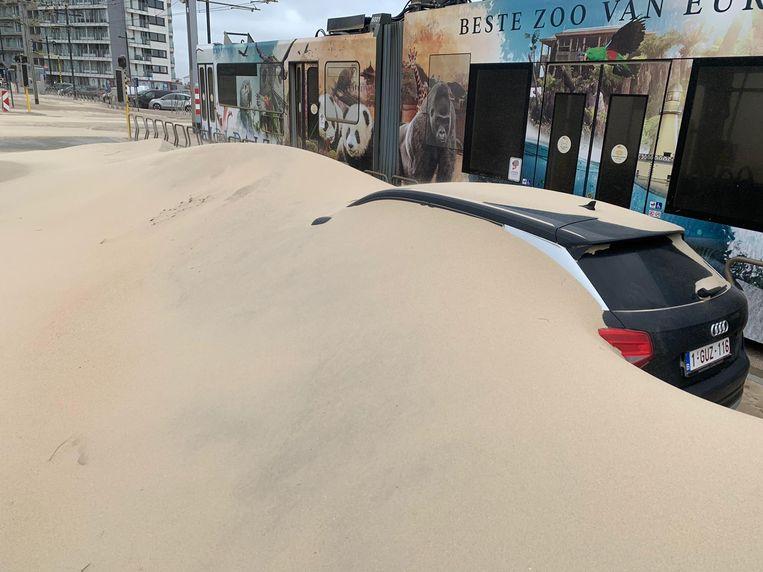 In Middelkerke werden auto's bedolven onder het zand. Beeld Benny Proot