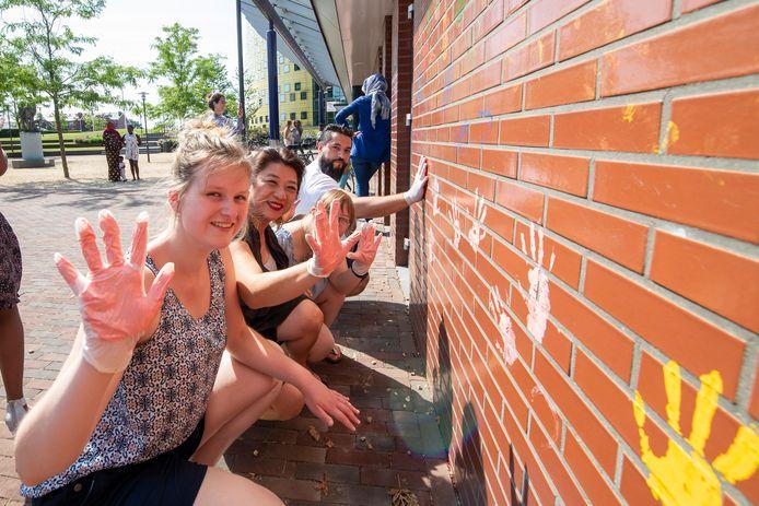 Cliënten van de ArtCrew, 't Gilde en InBeeld zetten in de zomer van 2019 met verf hun handdrukken op het gebouw van de oude Rabobank in Hardenberg. Anne van den Hoek (van InBeeld, tweede van links) helpt een handje.