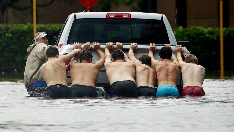 Enkele mannen proberen een vastgelopen pickup-truck voort te duwen in een ondergelopen straat. Beeld ap