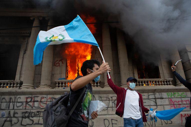 Terwijl de vlammen uit de gevel slaan van het parlementsgebouw in Guatemala-Stad, zwaaien demonstranten met de nationale vlag. Beeld AP