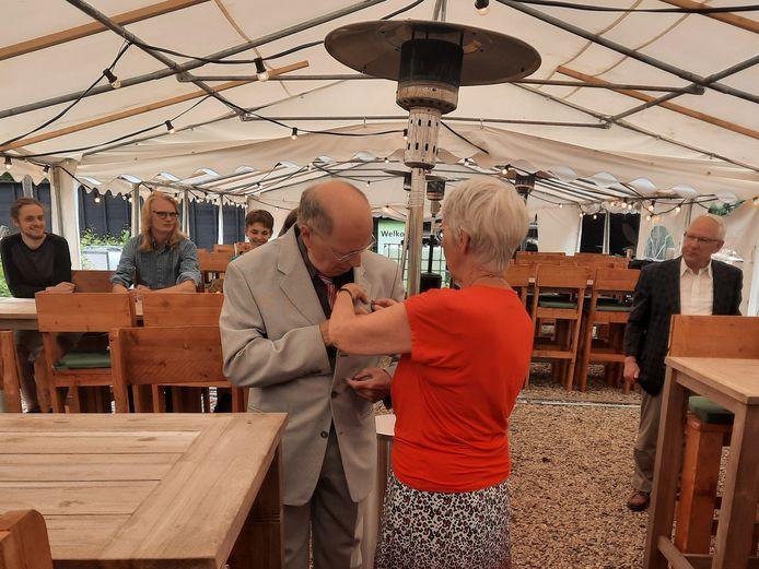 Gérard Hollanders krijgt de erespeld opgespeld door zijn vrouw.