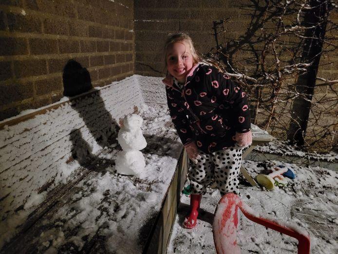 Sophie Gerritsen heeft in Wijchen haar eigen mini-sneeuwpop gemaakt. Er lag net  genoeg sneeuw.