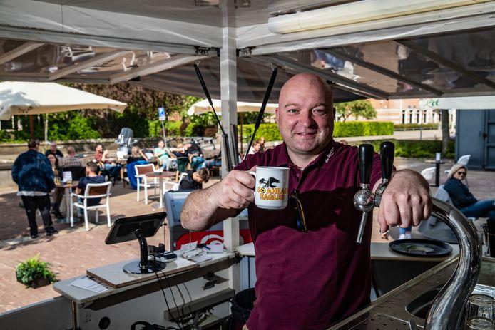 Uitbater Willem Jansen met Go Ahead-mok op het terras van café De Spaan in Zutphen. Zijn café vergaarde landelijke bekendheid nadat voormalig Go Ahead-speler Dzepar zijn 'beloning' uit de doeken deed op sportzender ESPN.