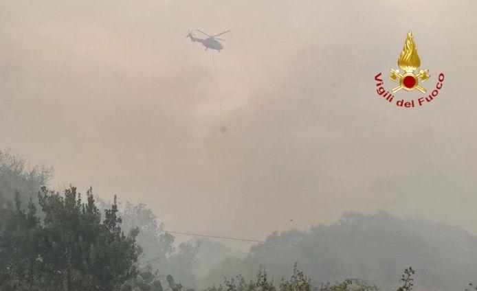 Een blushelikopter aan het werk bij de bosbrand rond de stad Oristano.