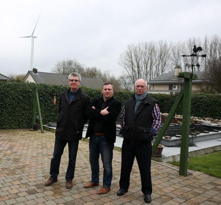 Guy Lories en schepen van Milieu Gunther Coppens in de tuin van Desidierius Boddengeen met op de achtergrond een van de windturbines van Eoly.