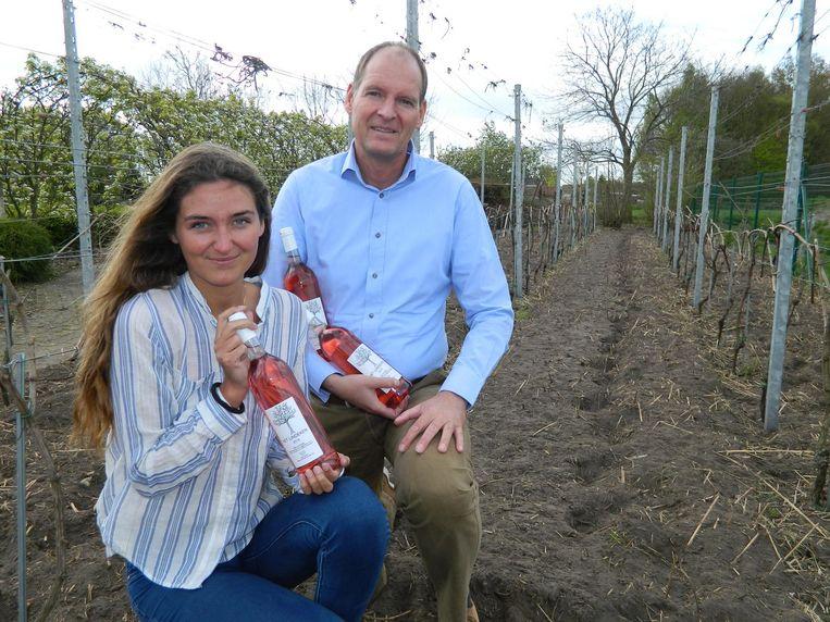 Frank Oosterlinck en dochter Valerie tussen de druivenranken. Over zes weken staan ze volop in bloei.