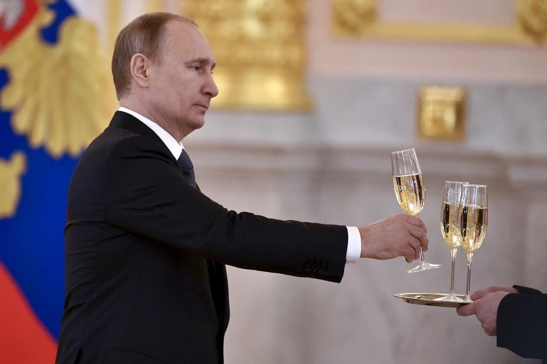 De Russische president Poetin krijgt een glas champagne aangereikt. Alleen Russische mousserende wijn mag voortaan 'champagne' heten in Rusland. Beeld Reuters