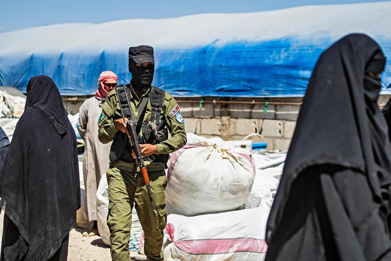 Een Koerdische bewaker tussen de vrouwen in het Al-Hol kamp.