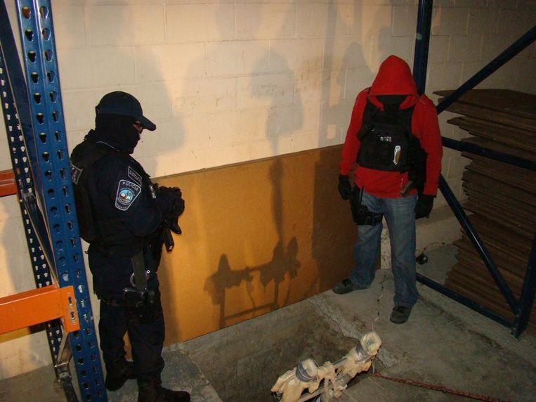 Politiemannen inspecteren de ingang van een nieuw ontdekte smokkeltunnel in Tijuana. Er werd 30 ton aan cannabis aangetroffen. Beeld epa