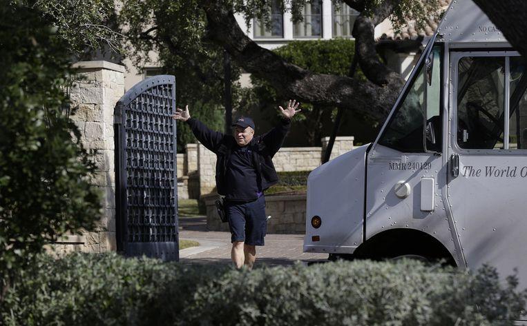 Een man die zojuist een pakketje heeft bezorgd bij de woning van Lance Armstrong, zwaait naar de cameraploegen en fotografen die zich voor de deur van de oud-renner hebben opgesteld. Beeld ap