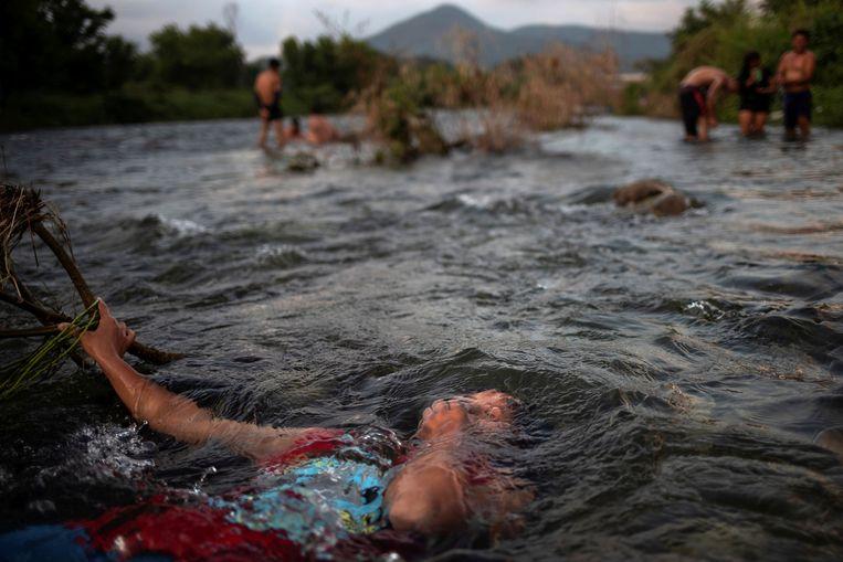 Jensi, een 14-jarige migrant uit Honduras, neemt een bad in een koele bergrivier in Pijijiapan, Mexico.  Beeld REUTERS