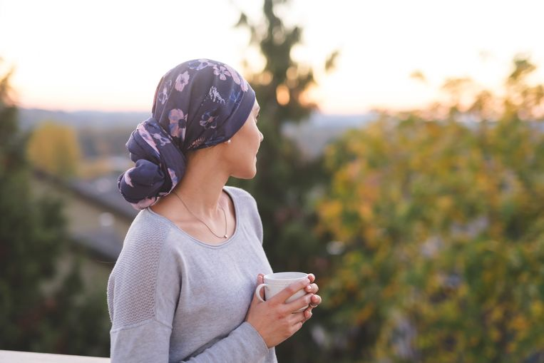 A beautiful young ethnic woman wearing a head wrap looks off in the distance and smiles contemplatively while drinking a cup of tea. She is standing outdoors and there are mountains and trees in the background. Beeld Getty Images
