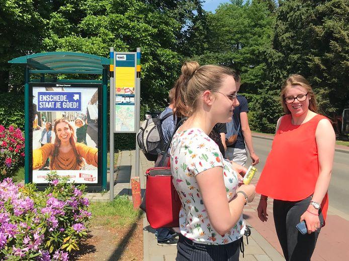 Leerlingen van het Rietveldcollege hebben niet in de gaten waar de reclameposter van Enschede op het bushokje over gaat. Foto DG