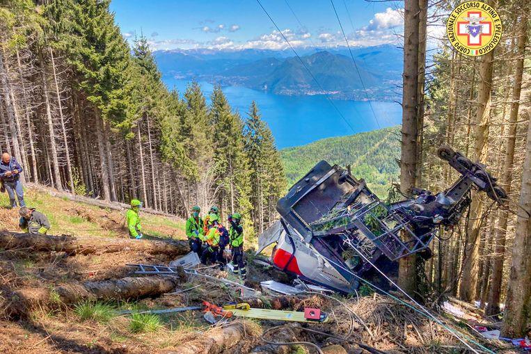 Reddingswerkers bij het wrak van de cabine die is neergestort nadat een kabel van de kabelbaan was gebroken.  Beeld AP