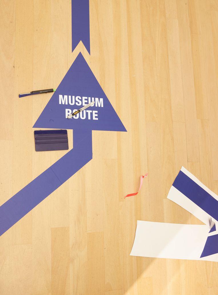 Blauwe pijlen door het gehele gebouw geven de looproute aan.  Beeld Henk Wildschut