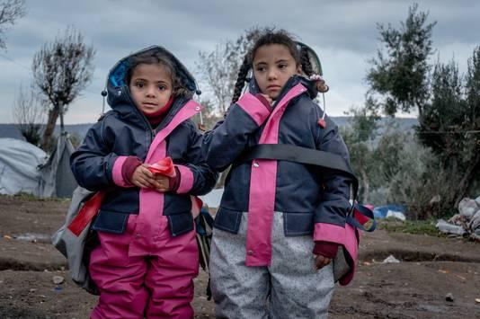Twee vluchtelingenkinderen op Lesbos hebben zojuist hun sheltersuit aangetrokken, die hen kan beschermen tegen de komende vrieskou.