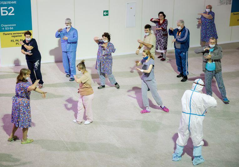 Met het coronavirus besmette patiënten volgen een les in de Chinese bewegingsleer tai chi in Moskou. Zij verblijven in de Krylatskoye-ijshal, waar in het verleden grote schaatskampioenschappen werden gereden – Sven Kramer werd er in 2012 wereldkampioen. De ijsbaan is omgebouwd tot tijdelijk ziekenhuis voor covidpatiënten.  Beeld REUTERS